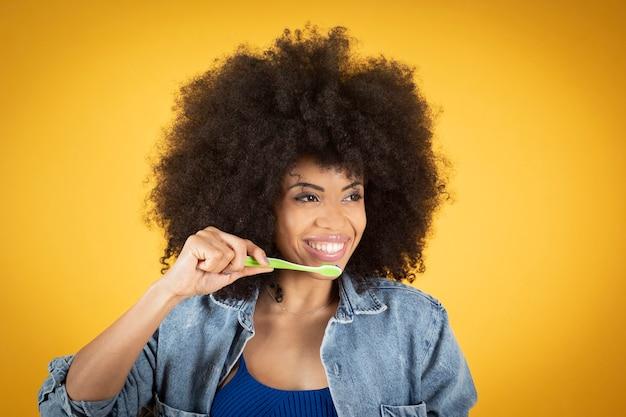 Bella donna afro utilizzando spazzolino da denti, donna nera con spazzolino da denti, sfondo giallo, denti bianchi.