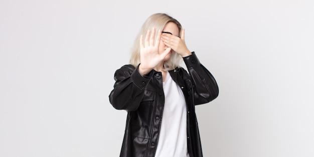 Bella donna albina che copre il viso con la mano e mette l'altra mano davanti per fermare la fotocamera, rifiutando foto o immagini