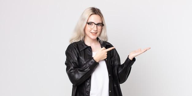 Bella donna albina che sorride allegramente e indica lo spazio della copia sul palmo sul lato, mostrando o pubblicizzando un oggetto