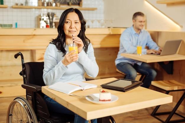 Donna disabile piuttosto vigile che si siede su una sedia a rotelle e beve succo mentre si lavora sul suo tablet in un caffè e un uomo seduto in background