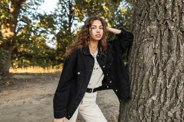 Ragazza modello abbastanza americana con i capelli ricci in una giacca nera di jeans con un maglione si erge e guarda la telecamera vicino a un albero in natura. stile femminile casual estivo e bellezza