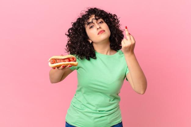 Bella donna araba che si sente arrabbiata, infastidita, ribelle e aggressiva e tiene in mano un hot dog