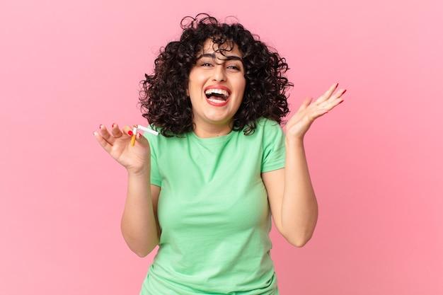 Bella donna araba che si sente felice e stupita per qualcosa di incredibile. concetto di non fumare
