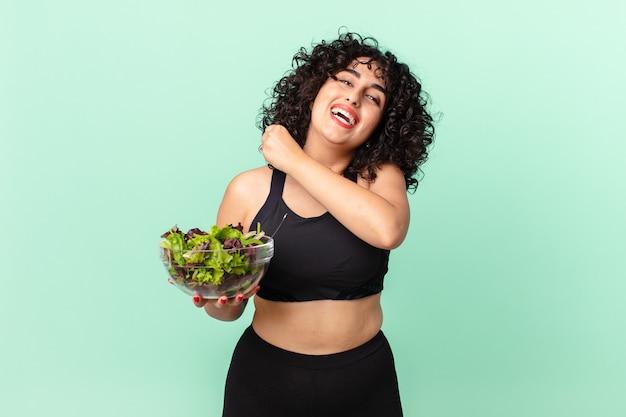 Bella donna araba che si sente felice e affronta una sfida o celebra e tiene in mano un'insalata. concetto di dieta