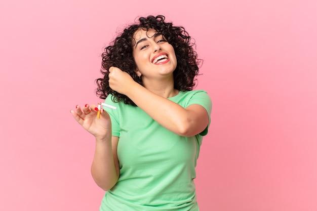 Bella donna araba che si sente felice e affronta una sfida o festeggia. concetto di non fumare