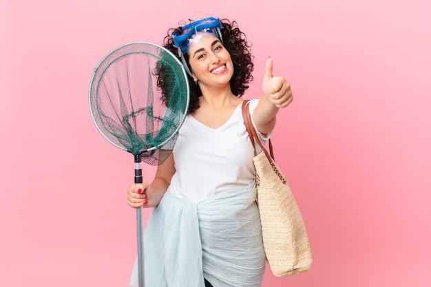 Bella donna araba che si sente orgogliosa, sorride positivamente con il pollice in alto con gli occhiali. concetto di pescatore