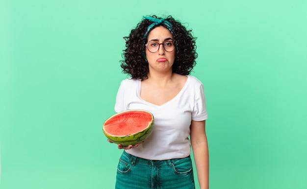 Bella donna araba che si sente triste e piagnucolona con uno sguardo infelice e piange e tiene in mano un'anguria. concetto di estate