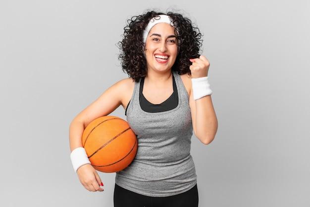 Bella donna araba che si sente scioccata, ride e celebra il successo e tiene in mano una palla da basket. concetto di sport