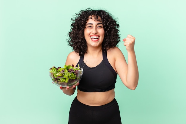 Bella donna araba che si sente scioccata, ride e celebra il successo e tiene in mano un'insalata. concetto di dieta