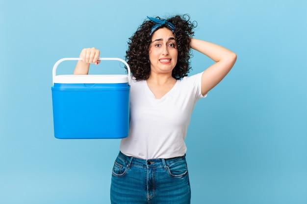Bella donna araba che si sente stressata, ansiosa o spaventata, con le mani sulla testa e con in mano un frigorifero portatile