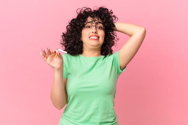 Bella donna araba che si sente stressata, ansiosa o spaventata, con le mani sulla testa. concetto di non fumare