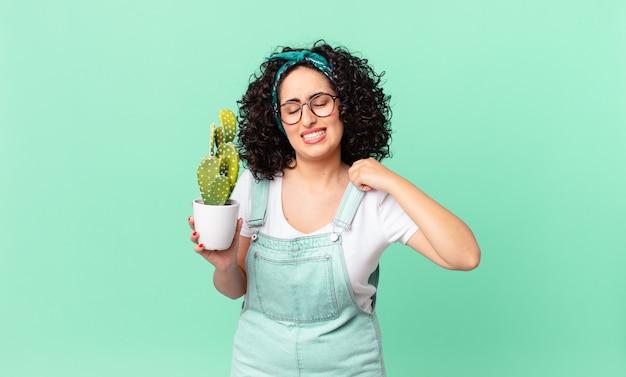 Bella donna araba che si sente stressata, ansiosa, stanca e frustrata e tiene in mano un cactus in vaso