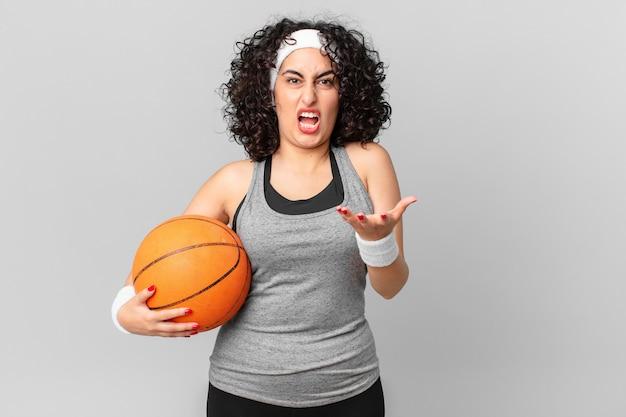 Bella donna araba che sembra arrabbiata, infastidita e frustrata e tiene in mano una palla da basket. concetto di sport