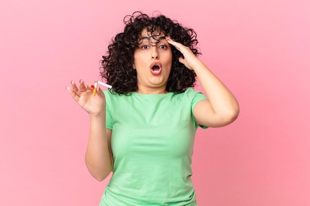 Donna abbastanza araba che sembra felice, stupita e sorpresa. concetto di non fumare