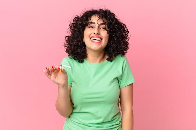 Donna abbastanza araba che sembra felice e piacevolmente sorpresa. concetto di non fumare