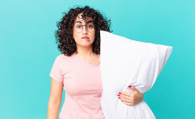 Donna abbastanza araba che sembra perplessa e confusa. in pigiama e con in mano un cuscino