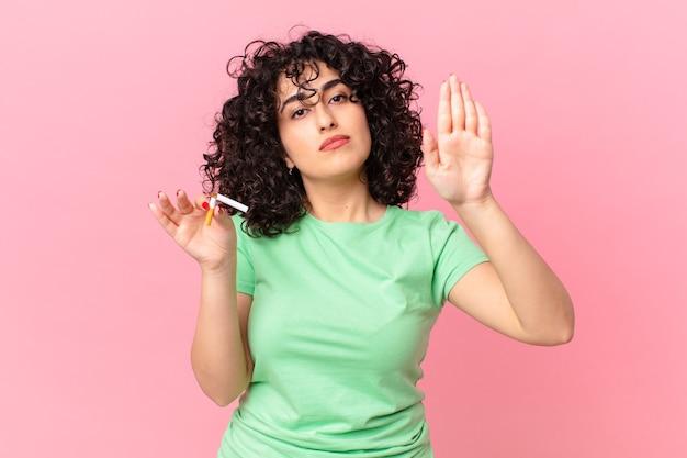 Donna abbastanza araba che sembra seria mostrando palmo aperto che fa gesto di arresto. concetto di non fumare