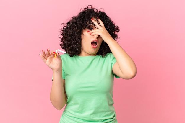 Bella donna araba che sembra scioccata, spaventata o terrorizzata, coprendo il viso con la mano. concetto di non fumare