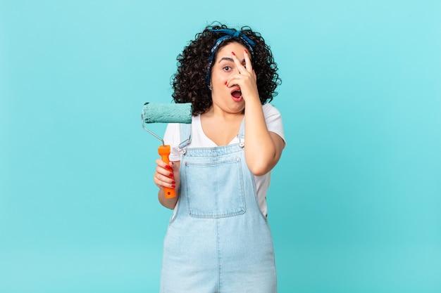 Bella donna araba che sembra scioccata, spaventata o terrorizzata, coprendo il viso con la mano. dipingere il concetto di casa