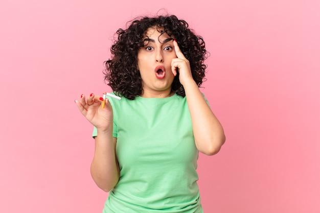 Bella donna araba che sembra sorpresa, realizzando un nuovo pensiero, idea o concetto. concetto di non fumare