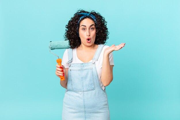 Bella donna araba che sembra sorpresa e scioccata, con la mascella caduta in possesso di un oggetto. dipingere il concetto di casa