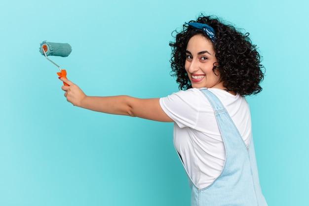 Bella donna araba che dipinge il concetto di muro di casa