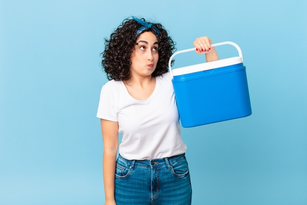Bella donna araba che alza le spalle, si sente confusa e incerta e tiene in mano un frigorifero portatile