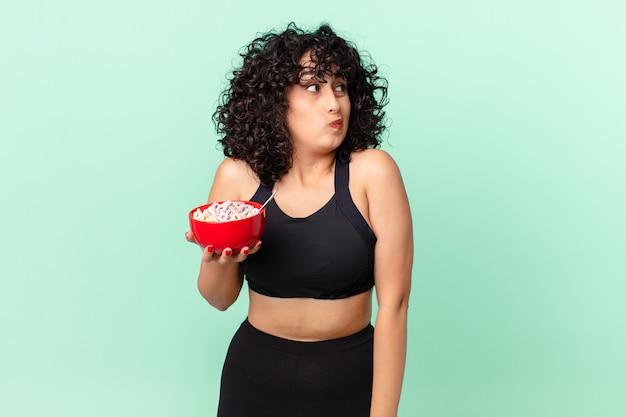 Bella donna araba che scrolla le spalle, si sente confusa e incerta indossando abiti da fitness e tenendo in mano una ciotola di fiocchi di mais