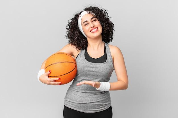 Bella donna araba che sorride allegramente, si sente felice e mostra un concetto e tiene in mano una palla da basket. concetto di sport