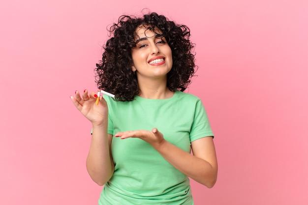 Bella donna araba che sorride allegramente, si sente felice e mostra un concetto. concetto di non fumare