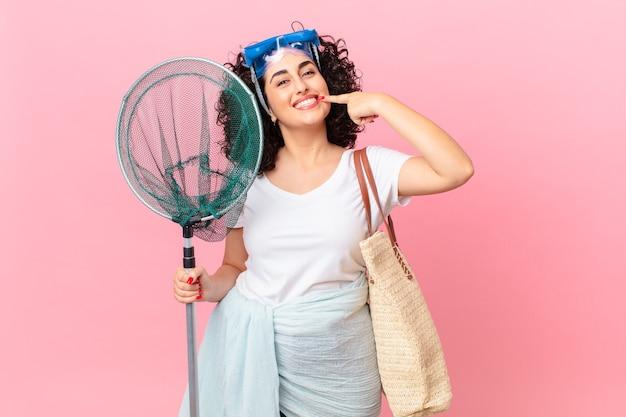 Bella donna araba che sorride con sicurezza indicando il proprio ampio sorriso con gli occhiali di protezione. concetto di pescatore