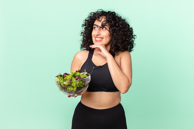 Bella donna araba che sorride felice e sogna ad occhi aperti o dubita e tiene in mano un'insalata. concetto di dieta