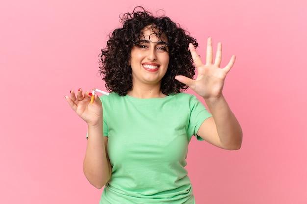 Donna abbastanza araba che sorride e che sembra amichevole, mostrando il numero cinque. concetto di non fumare