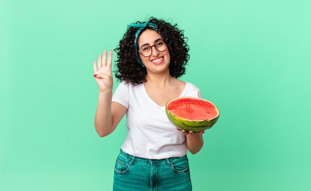 Bella donna araba che sorride e sembra amichevole, mostra il numero quattro e tiene in mano un'anguria. concetto di estate