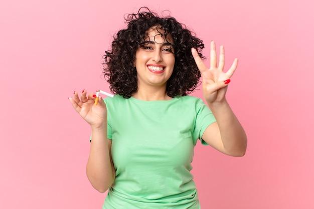 Donna abbastanza araba che sorride e che sembra amichevole, mostrando il numero quattro. concetto di non fumare