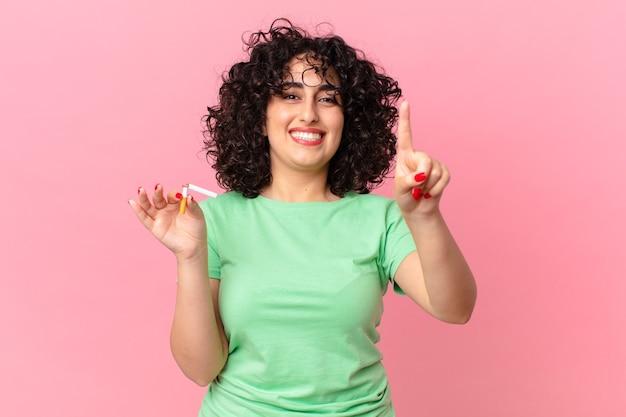 Donna abbastanza araba che sorride e che sembra amichevole, mostrando il numero uno. concetto di non fumare