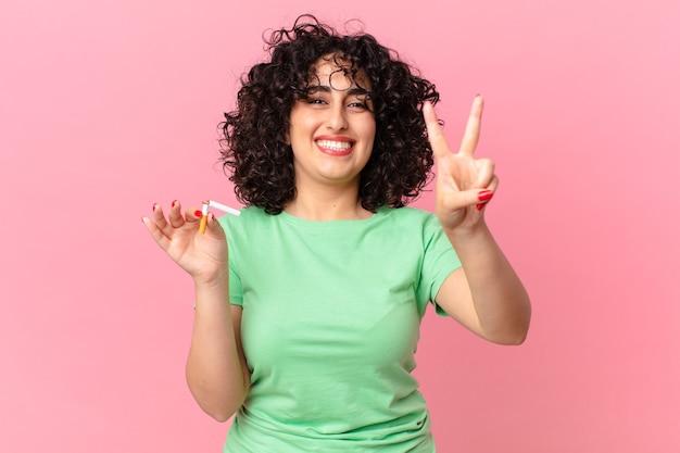 Donna abbastanza araba che sorride e che sembra amichevole, mostrando il numero due. concetto di non fumare