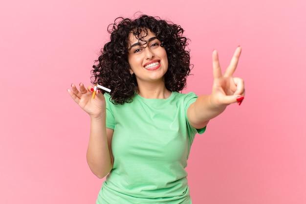 Bella donna araba che sorride e sembra felice, gesticolando vittoria o pace. concetto di non fumare