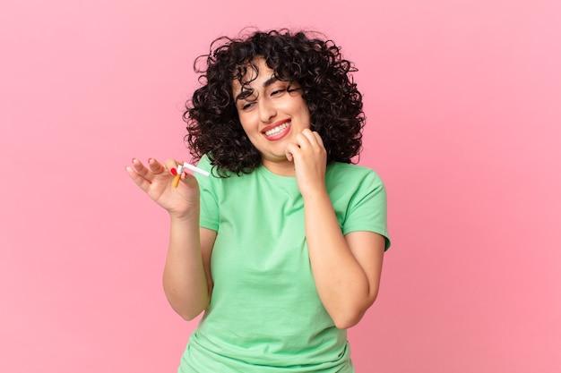 Donna abbastanza araba che sorride con un'espressione felice e sicura con la mano sul mento. concetto di non fumare