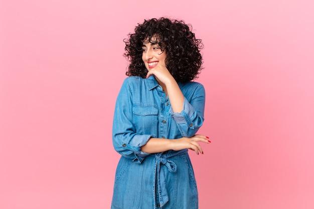 Bella donna araba che sorride con un'espressione felice e sicura con la mano sul mento