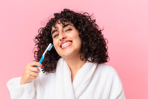 Bella donna araba che indossa accappatoio e usa uno spazzolino da denti
