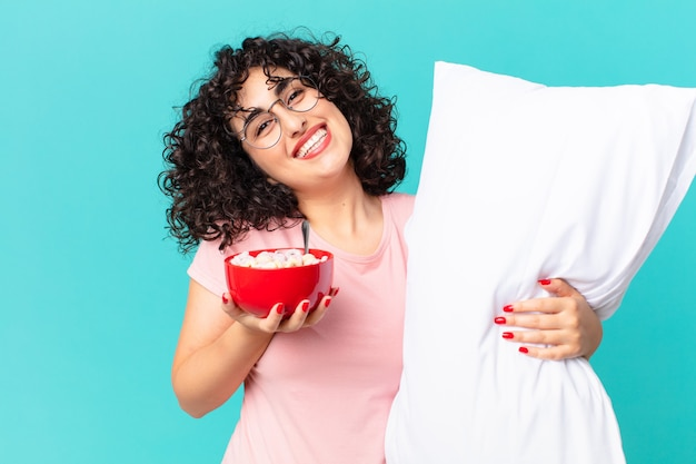 Bella donna araba che indossa un pigiama e con un cuscino.