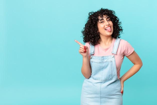 Bella donna araba con un atteggiamento allegro e ribelle, scherzando e tirando fuori la lingua