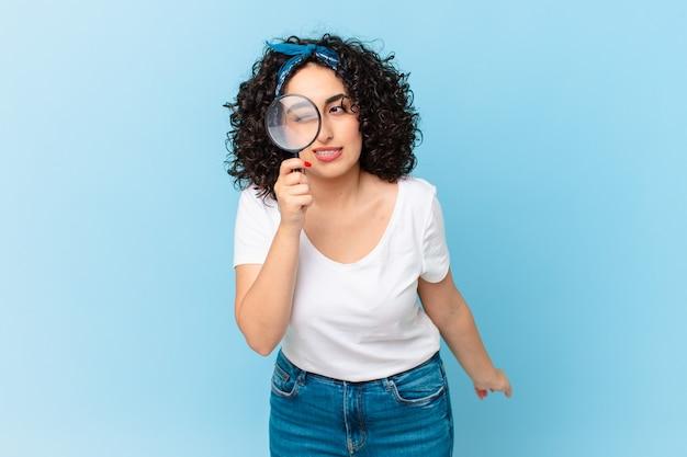 Bella donna araba con una lente d'ingrandimento