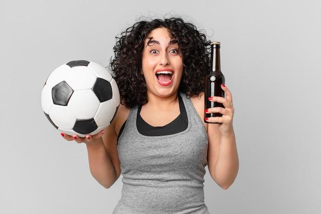 Bella donna araba con un pallone da calcio e bevendo una birra