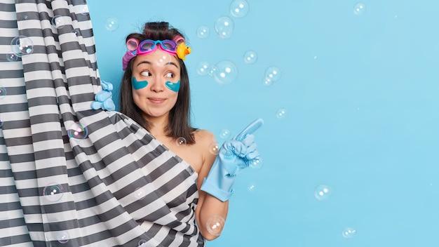 La modella femminile abbastanza asiatica si gode la routine di pulizia del corpo mattutina applica bigodini e cerotti sotto gli occhi si prepara per la data nasconde il corpo nudo dietro la tenda della doccia indica uno spazio vuoto.