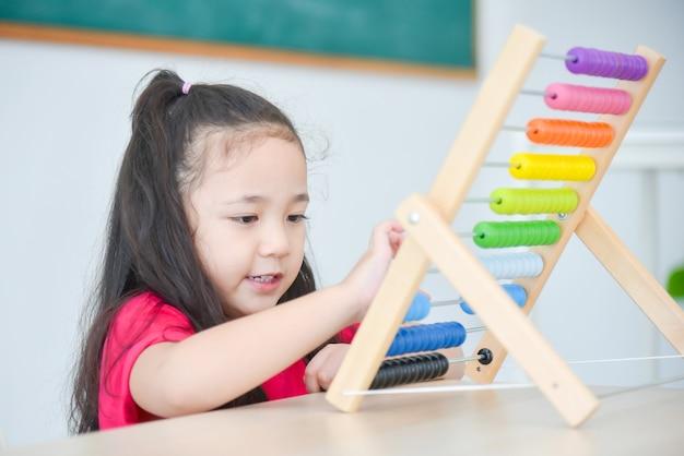 Ragazza abbastanza asiatica che conta il legno sull'abaco a scuola