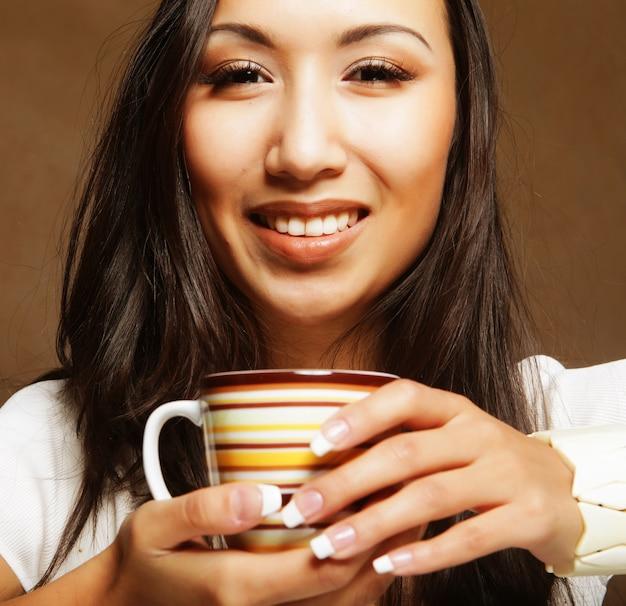 Donna abbastanza asiatica che beve caffè Foto Premium