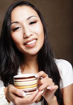 Donna abbastanza asiatica che beve caffè