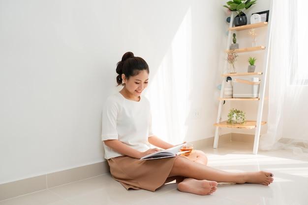 Bella donna asiatica che beve tè e legge un libro a casa